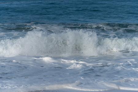 Foamy Atlantic ocean wave on Nazare city beach, Portugal. Reklamní fotografie