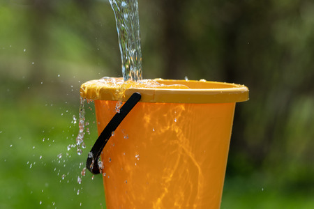 Pouring water and plastic bucket. Banco de Imagens - 121960619