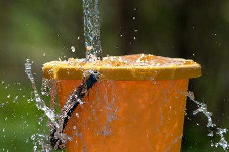 Verser de l'eau et un seau en plastique.