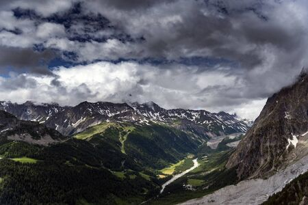 Alpine summits near Mont Blanc in clouds, Italy side. Stock Photo