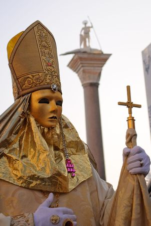 double cross: Mask posing in Venice carnival presenting religion