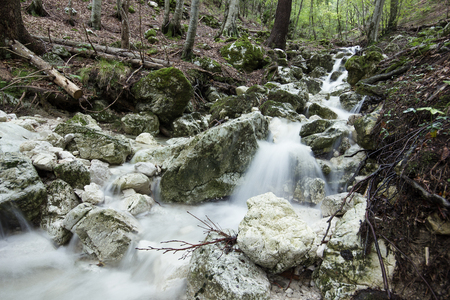 Dramaticly flowing creek in the forest making a little waterfall