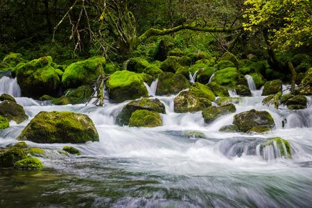 Dramaticly flowing river through rocks making cascade waterfall 版權商用圖片