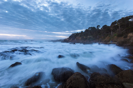 Dramatic ocean tide splashing water by rocky shore during sunset in California