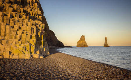 Beautiful sunset in black sand beach with huge cliffs, Iceland