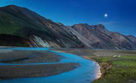 Night view of a colorful mountain ridge and river flowing down in the valley with sheep eating grass, Landmannalaugar, Iceland