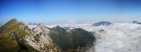 High mountain ridge hidden in the clouds during sunrise, Koschuta, Slovenia 版權商用圖片
