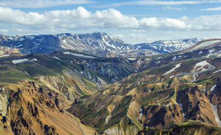 High colorful mountain ridge with mountain peaks covered by snow from summit of Blahnakur mountain, Landmannalaugar, Iceland
