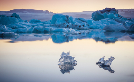 Two small pieces of ice flowing and reflecting in the cold lake with a big iceberg behind, jokulsarlon glacier lagoon, Iceland