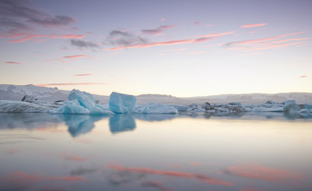 Giant pieces of ice flowing on and reflecting in a cold lake with a glacier behind, jokulsarlon glaciar lagoon, Iceland