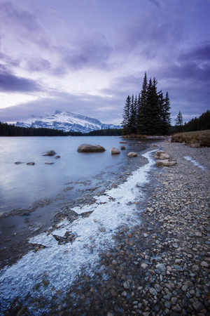 Icy path along the lake leading to a small island with trees and high snow covered mountains behind, Two Jack Lake, Banff National Park, Canada
