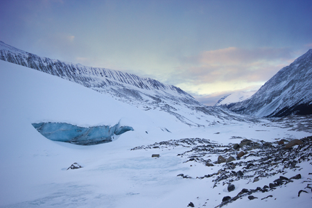 Big cold and blue ice cave in the athabasca glacier, during gentle sunset, Banff national park, Canada