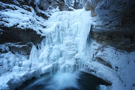Fast flowing water from a biog frozen waterfall with snow covered rocks around, Johnston Canyon, Banff National Park, Canada