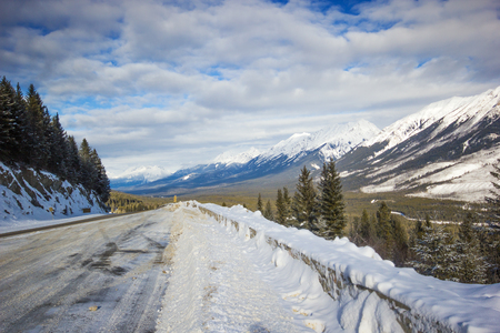 Narrow and slippery winter road with big snowbanks curving down from the mountain, Banff National Park, Canada Stock Photo