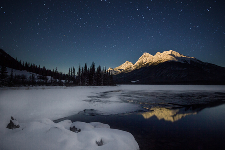 High snow covered mountain, in full moon light with a half frozen lake under night sky full of stars, Banff national park, Canada 版權商用圖片