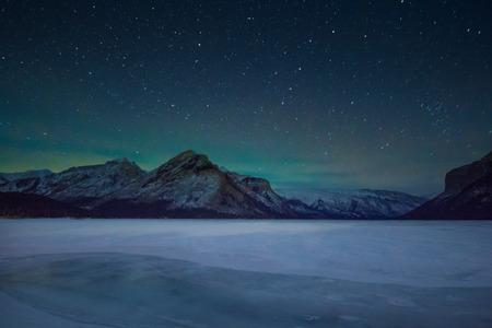 Northern lights - aurora borealis and sky full of stars above mountains and lake minewanka, Banff national park, Canada 版權商用圖片