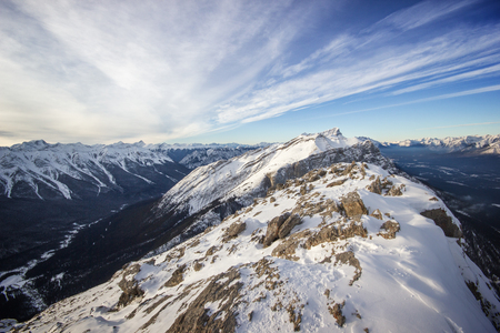 View to a deep winter valley from the top of the mountain ridge, Banff National Park, Canada