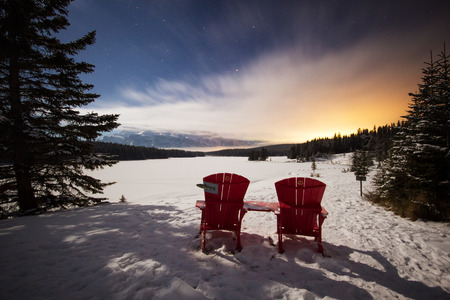 Two red chairs in the mountains view and view of the frozen lake under the umbrella night sky with the stars, moving clouds and last sun beams, Banff National Park, Canada