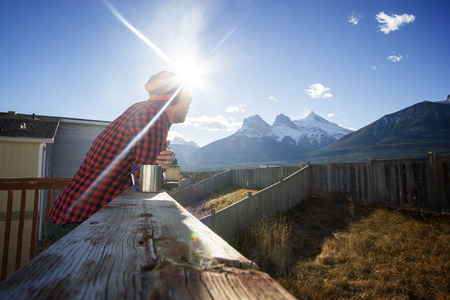 Young man standing on the patio and enjoying morning coffee with amazing view to high mountains - concept of inspiration, freedom, piece