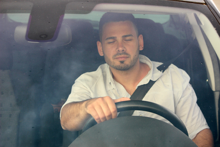 Tired man driving a car Stock Photo
