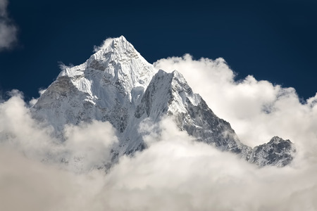 Snowcapped mountain peaks in the clouds. Stock Photo