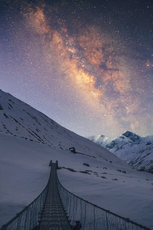 Bridge to the sky. Milky way under the snowy mountains in the night. Gangapurna 7455 m and Annapurna III 7555 m on the background. Stock Photo