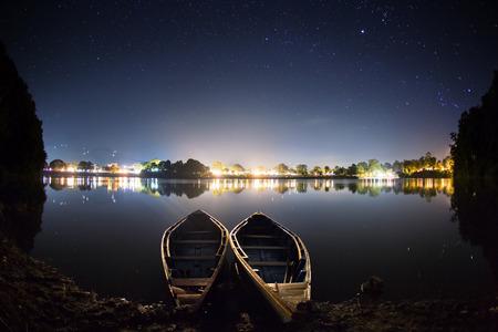 Twee boten op een water. Er zijn lichten van de stad op de achtergrond achter de Phewa meer het beroemdste meer in Pokhara Nepal.