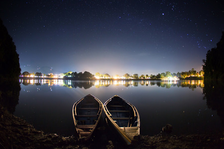 Two boats on a water. There are lights of the city on the background behind the Phewa lake  the most famous lake in Pokhara Nepal.