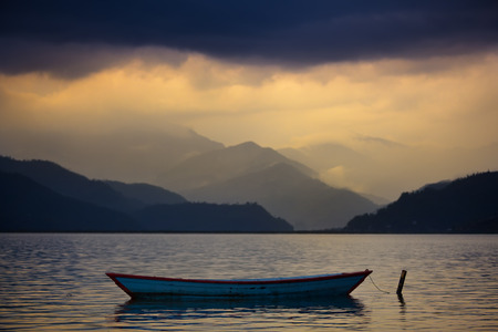 Boat on the serene water of the lake. Mountains and hills are behind it.