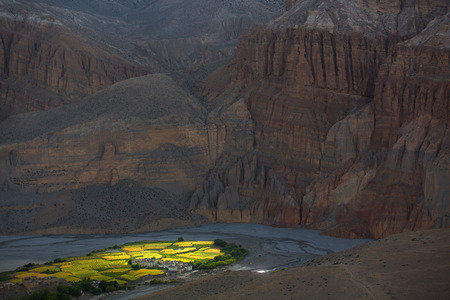 Beautiful green village that looks like an oasis down in the meadow between the huge gray rocky mountains of Himalayas. Nepal Upper Mustang Chhuksang village 2980m