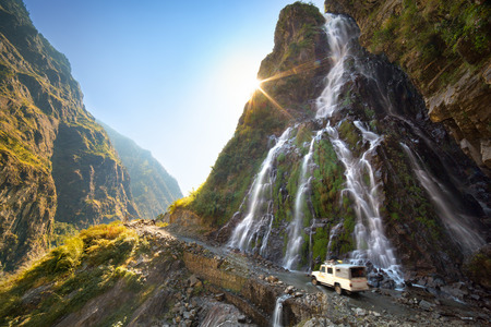 Car rides across the sunny mountain road beneath the waterfall in Nepal Himalayas Annapurna Conservation Area.