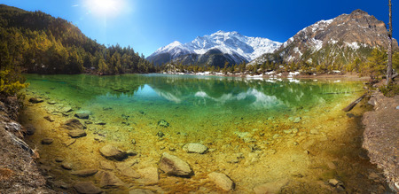 Beautiful mountain lake with crystal clear water surrounded by hills and mountains. Nepal Annapurna region Mring lake 3270 m and Annapurna II 7937 m
