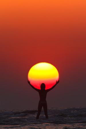 Een vrouw lijkt de zon in haar handen op de zonsondergang in India Maharashtra Paradise Beach te houden. Stockfoto - 41645549