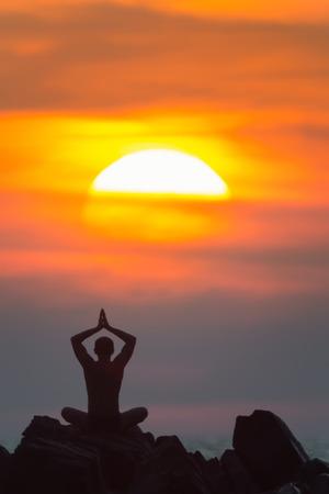 namaskar: A silhouette of the man meditating on the rocks outdoors.