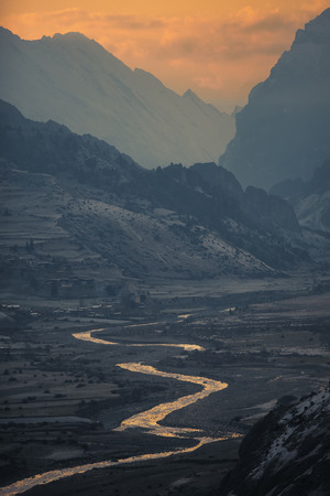 The river flows at the foot of the mountains. Nepal ACAP view of Marsyangdi river and Bragha village from the Manang 3540 m