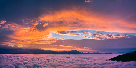 Bright and colorful sunset over the sea of clouds. Panoramic view in violet orange and pink colors.