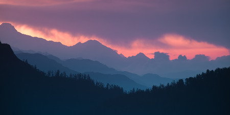 Panoramic Himalayan hills and mountains topped with a colorful dramatic sky.