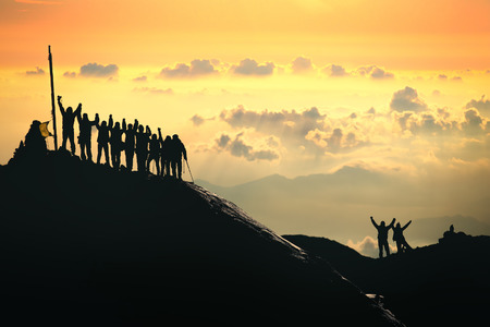 groups: A group of people are standing on the top of the mountain.