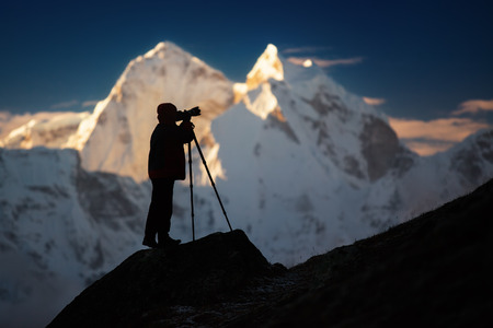 A silhouette of a man photographer standing on a hills in front of the mountains.