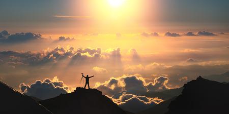 雲の上の山の上に立っている男性。