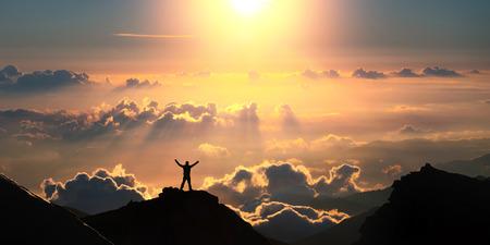 Op de bovenkant van de wereld. Een man die op de top van de berg boven de wolken met een rised handen. Stockfoto