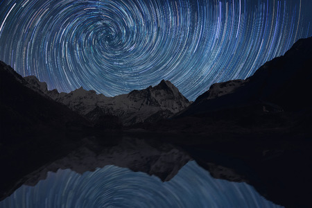 Star trails over the mountains and a lake reflected in water.