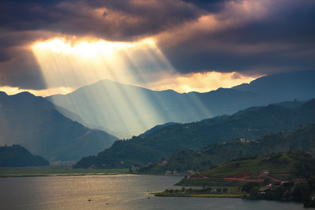 Sunlight visible from the clouds over the hills and lake.