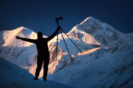 A person is standing in front of the mountains in snow holding tripod in his hands.