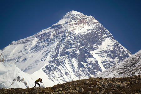 A man is standing in front of Mt. Everest. Nepal, Everest region Sagarmatha National Park, Everest 8,850 m.
