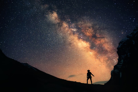 Guardian of the Galaxy. A man is standing next to the Milky Way galaxy. Stock Photo