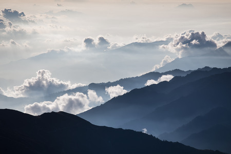 Brightly lit fog and cloud mountain valley landscape.