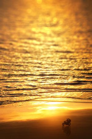 Taste of Freedom. Mensen rijden een motorfiets op de zonsondergang over het strand in de buurt van de eindeloze zee.