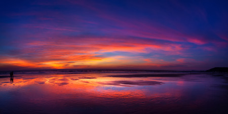 Really bright and colorful sunset at the sea with reflection of the skies in the water.
