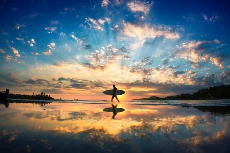 aventura: surfista sol. Un hombre está caminando con una tabla de surf en sus manos a través de la orilla del mar. Foto de archivo